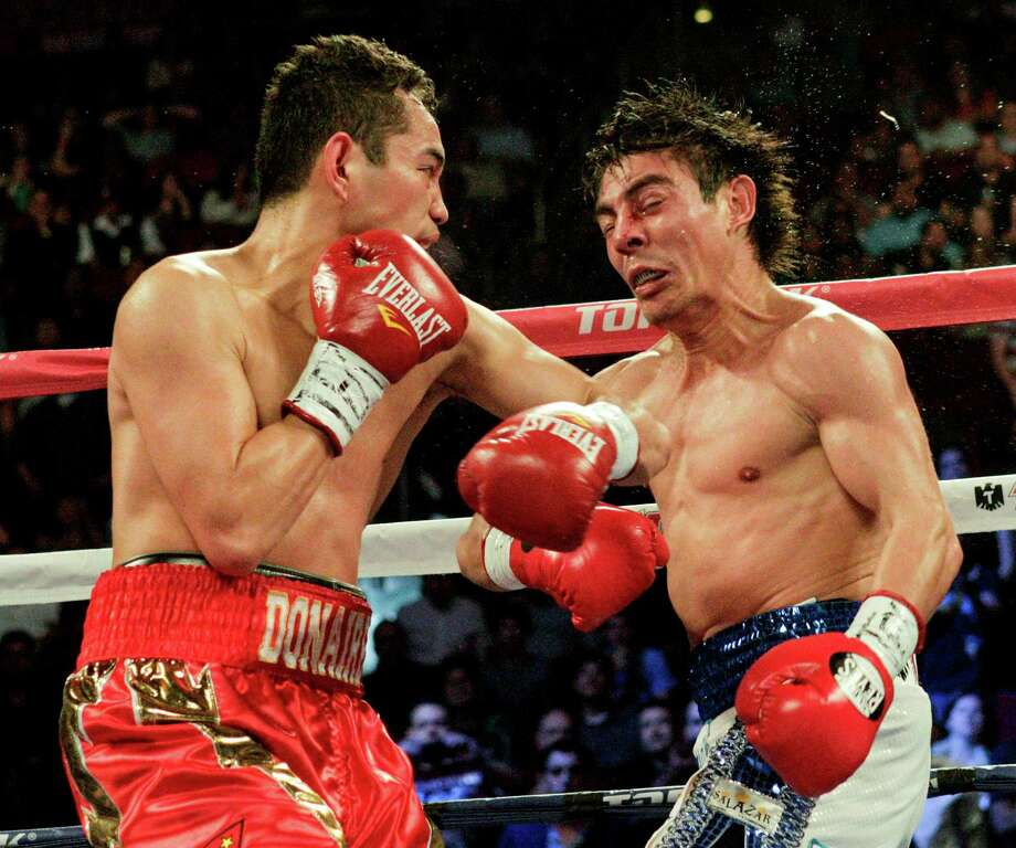 Nonito Donaire, left, delivers a left hook to end Jorge Arce's night. Donaire defended his WBO super bantamweight title with the knockout at Toyota Center. Photo: Bob Levey, Photographer / ©2012Bob Levey