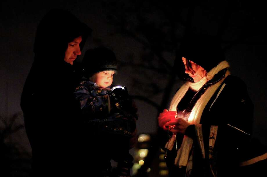 Andy, his son Kiran, 3, and his wife Amy stand in silence as they attend a candlelight vigil in remembrance of the Newtown, Conn. shooting victims at Green Lake Park in Seattle on Saturday, December 15, 2012. The vigil was held after a gunman killed his mother and then killed 20 children and six adults at Sandy Hook Elementary in Connecticut before taking his own life. Photo: LINDSEY WASSON / SEATTLEPI.COM