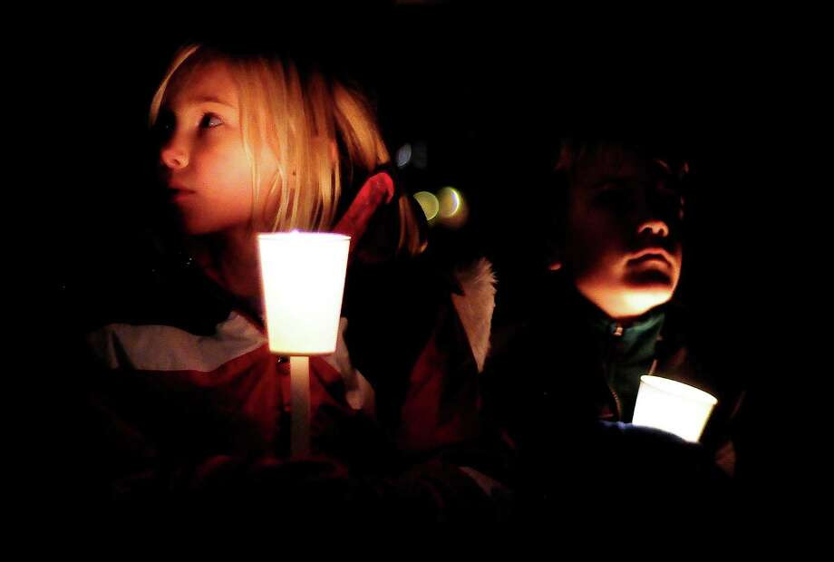 Scout Elizabeth Noble, 7, and her brother Jack Noble, 9, crouch silently during a candlelight vigil in remembrance of the Newtown, Conn. shooting victims at Green Lake Park in Seattle on Saturday, December 15, 2012. The vigil was held after a gunman killed his mother and then killed 20 children and six adults at Sandy Hook Elementary in Connecticut before taking his own life. Photo: LINDSEY WASSON / SEATTLEPI.COM