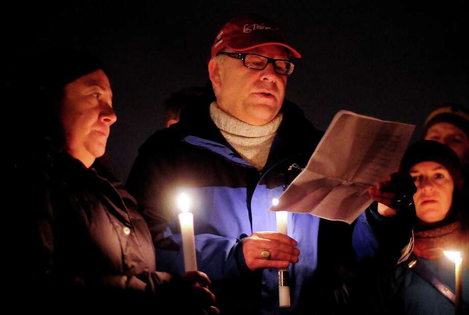People pass around a list of the victims, saying one name aloud each, during a candlelight vigil in remembrance of the Newtown, Conn. shooting victims at Green Lake Park in Seattle on Saturday, December 15, 2012. The vigil was held after a gunman killed his mother and then killed 20 children and six adults at Sandy Hook Elementary in Connecticut before taking his own life. Photo: LINDSEY WASSON / SEATTLEPI.COM