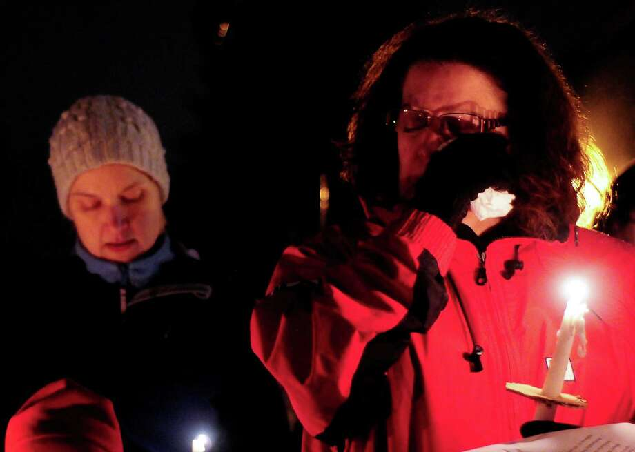 A woman wipes away ears as her candle begins to burn down during a candlelight vigil in remembrance of the Newtown, Conn. shooting victims at Green Lake Park in Seattle on Saturday, December 15, 2012. The vigil was held after a gunman killed his mother and then killed 20 children and six adults at Sandy Hook Elementary in Connecticut before taking his own life. Photo: LINDSEY WASSON / SEATTLEPI.COM