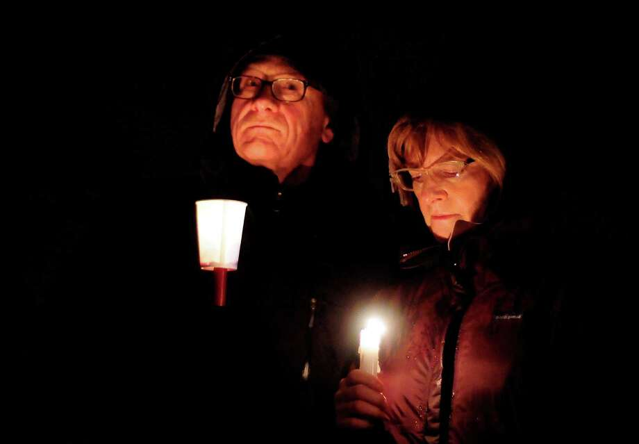 A couple is lit only by their candles as they stand in the dark during a candlelight vigil in remembrance of the Newtown, Conn. shooting victims at Green Lake Park in Seattle on Saturday, December 15, 2012. The vigil was held after a gunman killed his mother and then killed 20 children and six adults at Sandy Hook Elementary in Connecticut before taking his own life. Photo: LINDSEY WASSON / SEATTLEPI.COM
