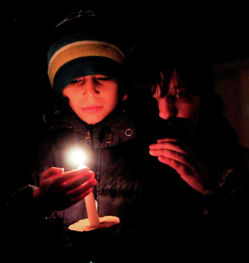 Katrina Marrow, 13, right, comforts her friend Julian Shah, 7, during a candlelight vigil in remembrance of the Newtown, Conn. shooting victims at Green Lake Park in Seattle on Saturday, December 15, 2012. The vigil was held after a gunman killed his mother and then killed 20 children and six adults at Sandy Hook Elementary in Connecticut before taking his own life. Photo: LINDSEY WASSON / SEATTLEPI.COM
