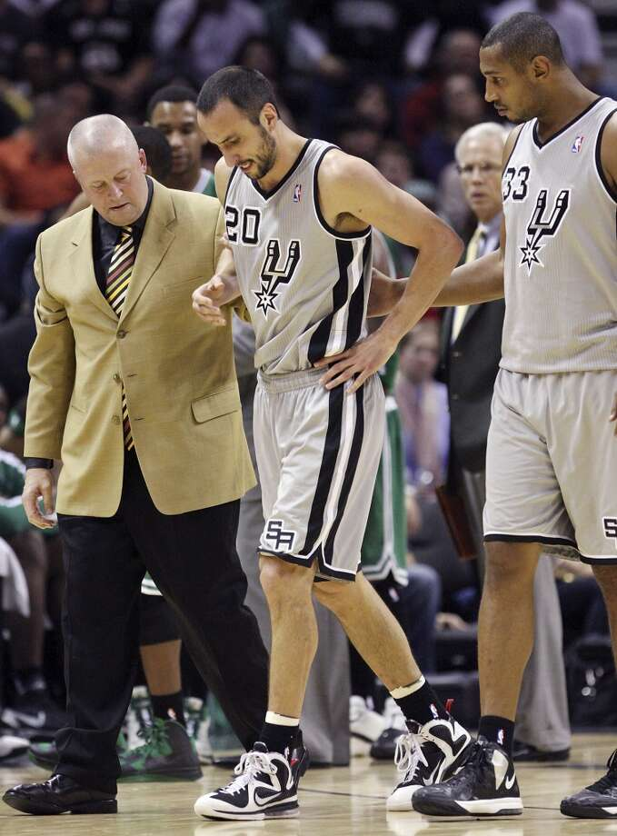 San Antonio Spurs' Manu Ginobili (center) is helped off the court by athletic trainer Will Sevening (left) and San Antonio Spurs' Boris Diaw after being injured during first half action against the Boston Celtics Saturday Dec. 15, 2012 at the AT&T Center. (Edward A. Ornelas / San Antonio Express-News)