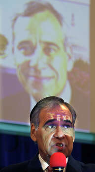 "With a digital projector casting ""Texas"" on his forehead, U.S. Rep. Charlie Gonzalez, D-San Antonio, speaks at a forum  at The Neighborhood Place on July 12, 2008 about the upcoming digital television conversion. Photo: Bob Owen, San Antonio Express-News / rowen@express-news.net"