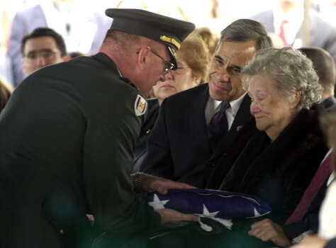 U.S. Rep. Charlie Gonzalez and his mother Bertha Gonzalez receive the flag that had been covering father and husband Henry B. Gonzalez's casket at the late former congressman's burial at San Fernando Cemetery No. 2 on Dec. 2, 2000. Photo: San Antonio Express-News File Photo / SAN ANTONIO EXPRESS-NEWS