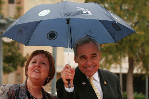 U.S. Rep. Charlie Gonzalez, D-San Antonio, keeps an unidentified woman dry during a rally in support of State Children's Health Insurance Program legislation in Congress at Milam Park on Nov. 17, 2007. Photo: San Antonio Express-News File Photo / SAN ANTONIO EXPRESS-NEWS