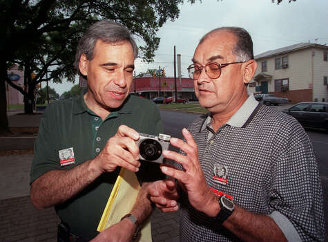 Congressional hopeful Charlie Gonzalez shows a volunteer worker and friend, Bobby Guerrero, how to use Gonzalez's camera, so Guerrero can take a photo of Gonzalez and a campaign worker on April 14, 1998. Photo: San Antonio Express-News File Photo / SAN ANTONIO EXPRESS-NEWS