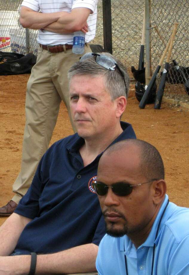 Astros general manager Jeff Luhnow, sitting left, watches practice Monday at Houston's Dominican Republic instructional academy in Guerra, Santo Domingo.  (Brian T. Smith/Houston Chronicle)