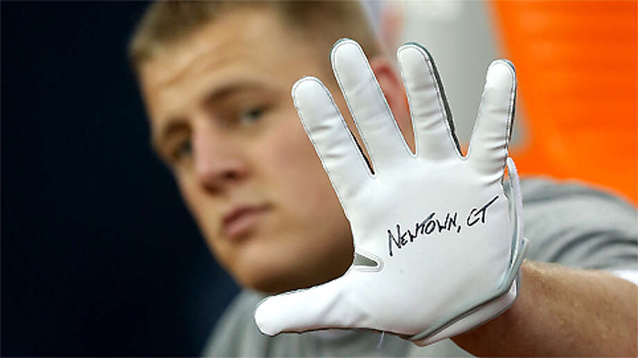J.J. Watt of the Houston Texans displays a glove to remember the victims of the massacre at Sandy Hook Elementary School in Newtown, Connecticut prior to the start of the game against the Indianapolis Colts at at Reliant Stadium on December 16, 2012 in Houston, Texas. Photo: Scott Halleran, . / 2012 Getty Images