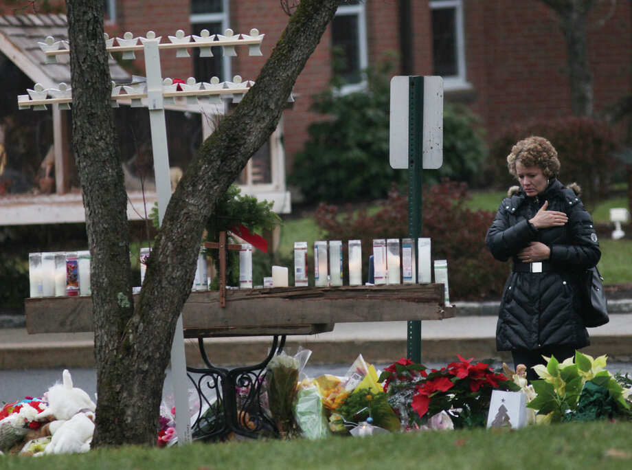 A woman prays at a memorial outside of St. Rose of Lima Church in the Sandy Hook section of Newtown, Conn. on Sunday, Dec. 16, 2012. Photo: BK Angeletti, B.K. Angeletti / Connecticut Post freelance B.K. Angeletti