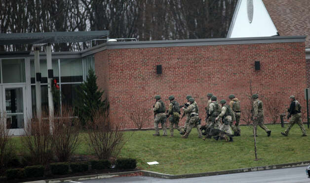 State police enter a building on the St. Rose of Lima Church campus in the Sandy Hook section of Newtown, Conn. after an unspecified threat on Sunday, Dec. 16, 2012. Parishioners were evacuated during noon mass. Photo: BK Angeletti, B.K. Angeletti / Connecticut Post freelance B.K. Angeletti