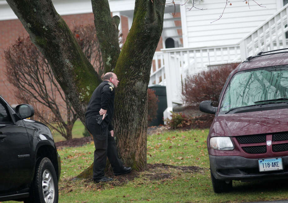 A police officer stands outside as state police enter a building on the St. Rose of Lima Church campus in the Sandy Hook section of Newtown, Conn. after an unspecified threat on Sunday, Dec. 16, 2012. Parishioners were evacuated during noon mass. Photo: BK Angeletti, B.K. Angeletti / Connecticut Post freelance B.K. Angeletti