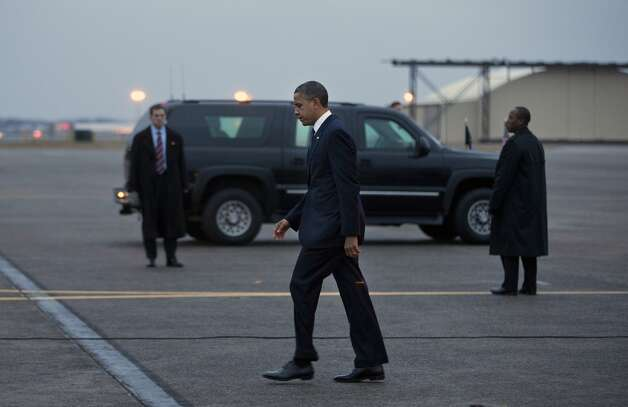 President Barack Obama walks to his car after arriving at Bradley Air National Guard Base to attend an interfaith vigil for the victims of the Sandy Hook Elementary School shooting in Newtown on Sunday, Dec. 16, 2012 in East Granby, Conn. A gunman walked into Sandy Hook Elementary School in Newton, Conn., on Friday and opened fire, killing 26 people, including 20 children.  Photo: Evan Vucci, Associated Press