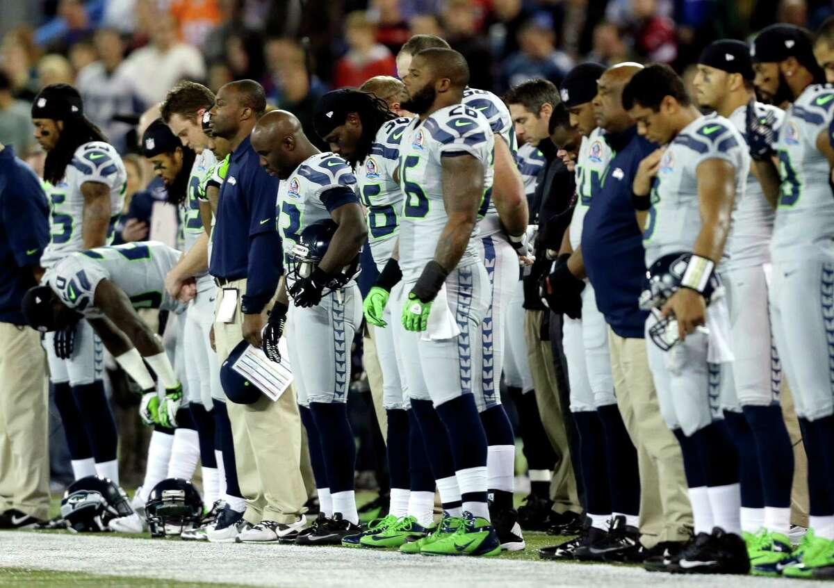 Seattle Seahawks players observe a moment of silence for the victims of the Sandy Hook Elementary School shootings before an NFL football game against the Buffalo Bills, Sunday, Dec. 16, 2012, in Toronto.