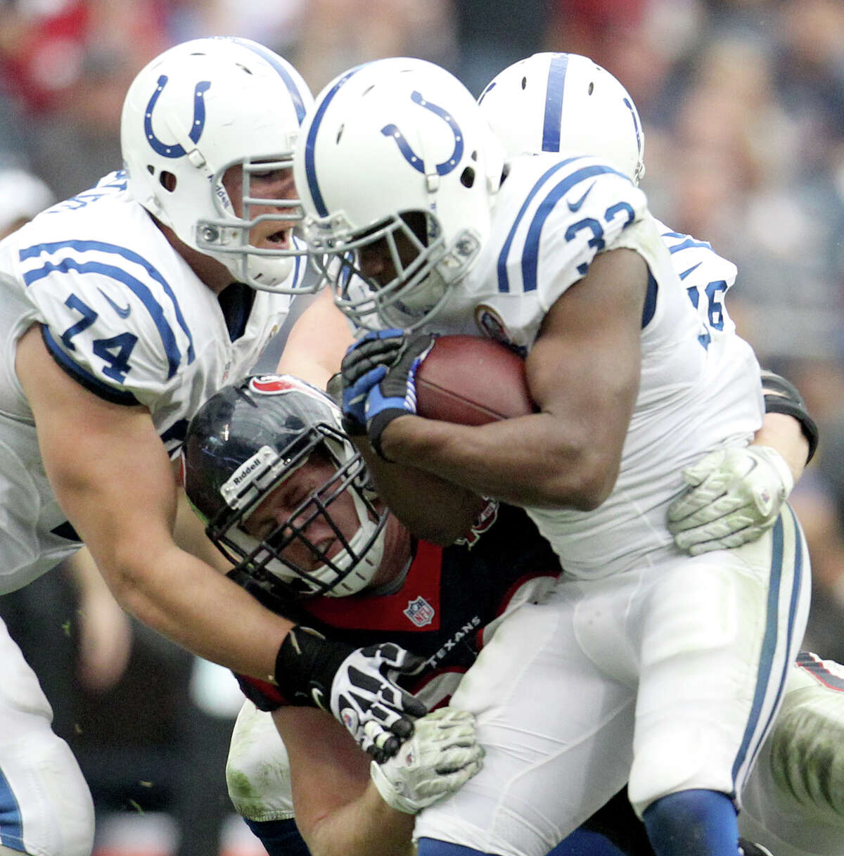 Indianapolis Colts running back Vick Ballard (33) is stopped by Houston Texans defensive end J.J. Watt (99) during the second quarter of an NFL football game at Reliant Stadium, Sunday, Dec. 16, 2012, in Houston.