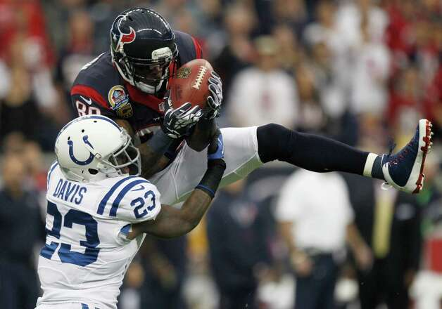 Houston Texans wide receiver Andre Johnson (80) makes a midfield catch over Indianapolis Colts cornerback Vontae Davis (23) defends during the first quarter at Reliant Stadium on Sunday, Dec. 16, 2012, in Houston. Photo: Brett Coomer, Houston Chronicle / © 2012  Houston Chronicle