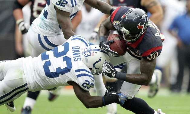 Indianapolis Colts cornerback Vontae Davis (23) tries to bring down Houston Texans wide receiver Andre Johnson (80) after a first down catch during the second quarter of a NFL football game, Sunday, Dec. 16, 2012, in Reliant Stadium in Houston. Photo: Nick De La Torre, Houston Chronicle / © 2012  Houston Chronicle