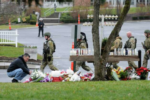 Armed State Police members file past a memorial to the victims of Sandy Hook Elementary School, Sunday Dec. 16, 2012, at Saint Rose of Lima Catholic Church in Newtown, Conn. Police responded to a threat called in at the Church. It was evacuated in the middle of Sunday services. Photo: Will Waldron, Hearst Newspapers/Will Waldron / The News-Times