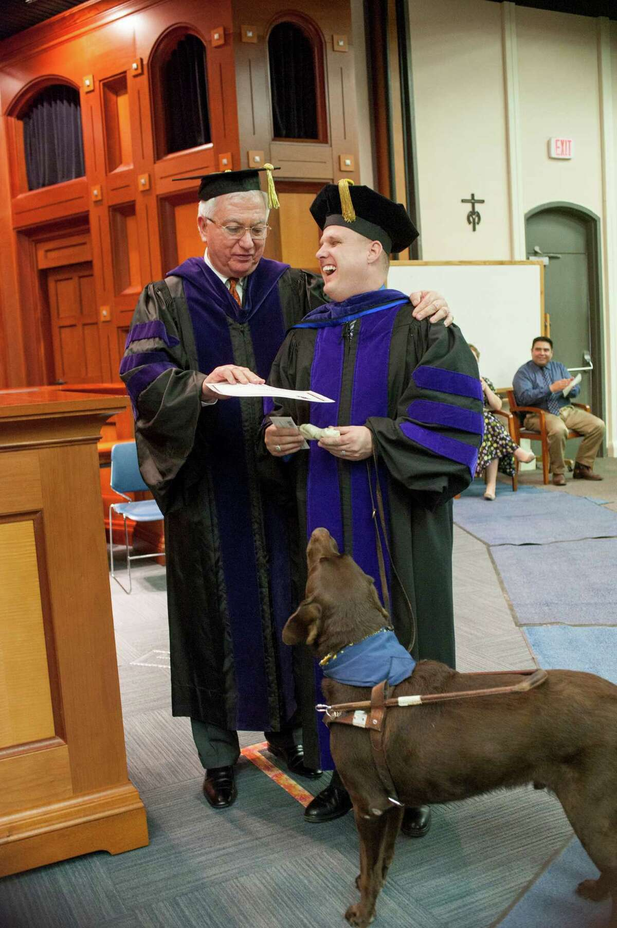 Charles Cantu, dean of St. Mary's University's School of Law, honors Robert Dittman, 35, for completing his law degree and presents his seeing-eye dog Snickers with a bone and a certificate and called him 'the most popular student in law school' at ceremony Dec. 8, 2012. Dittman is blind but aspires to become a military attorney. Photo credit: Melanie Davis and St. Mary's University