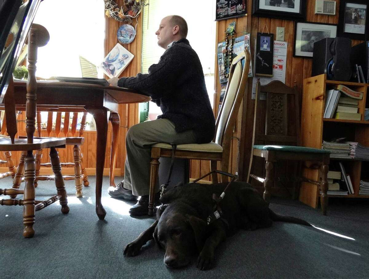 Robert Dittman studies for the Texas Bar Exam, accompanied by his dog, Snickers, at Buon Giorno on Tuesday, Dec. 11, 2012. Dittman has many accomplishments to his credit, despite his blindness.
