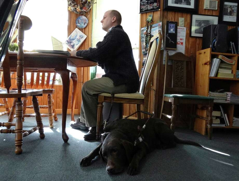 Robert Dittman studies for the Texas Bar Exam, accompanied by his dog, Snickers, at Buon Giorno on Tuesday, Dec. 11, 2012. Dittman has many accomplishments to his credit, despite his blindness. Photo: Billy Calzada, San Antonio Express-News / SAN ANTONIO EXPRESS-NEWS