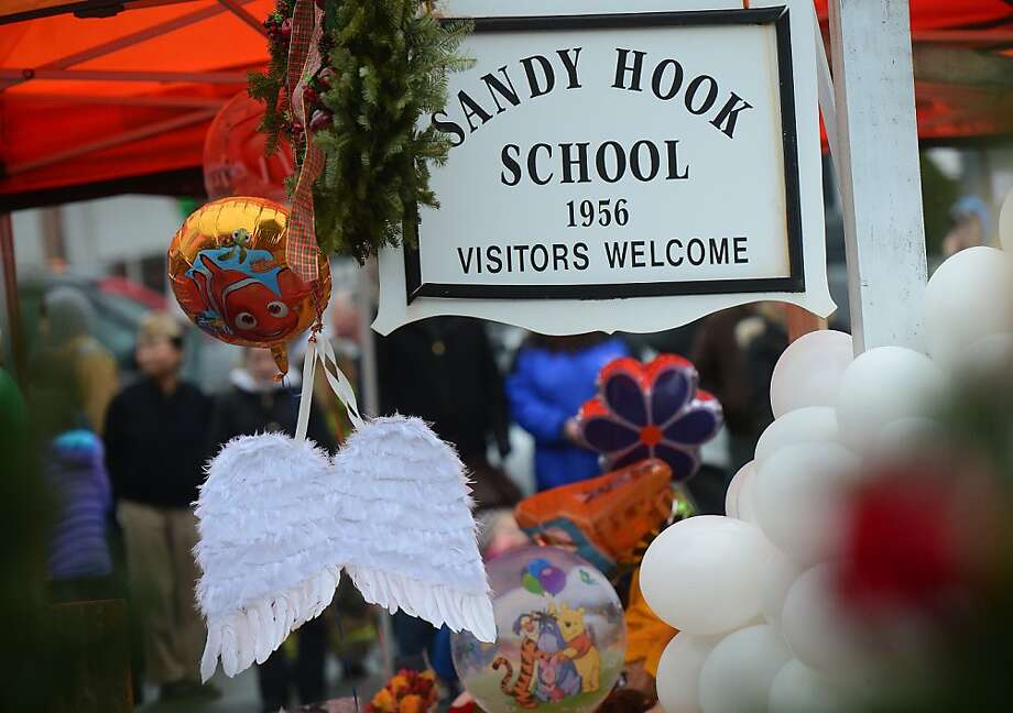 A pair of angel wings and balloons stand after being offered at a makeshift shrine to the victims of a elementary school shooting in Newtown, Connecticut, December 16, 2012.  A young gunman slaughtered 20 small children and six teachers on December 14,2012 after walking into a school in an idyllic Connecticut town wielding at least two sophisticated firearms. AFP PHOTO/Emmanuel DUNANDEMMANUEL DUNAND/AFP/Getty Images Photo: Emmanuel Dunand, AFP/Getty Images