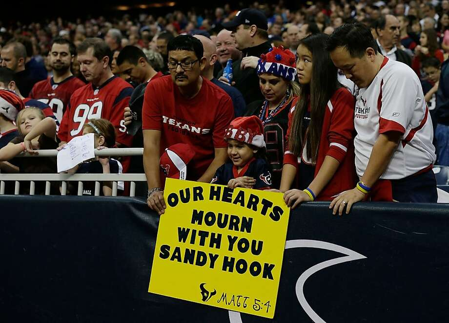 HOUSTON, TX - DECEMBER 16:  Houston Texans fans take a moment to remember the victims of a massacre at Sandy Hook Elementary School in Newtown, Connecticut prior to the start of the game against the Indianapolis Colts at at Reliant Stadium on December 16, 2012 in Houston, Texas.  (Photo by Scott Halleran/Getty Images) Photo: Scott Halleran, Getty Images