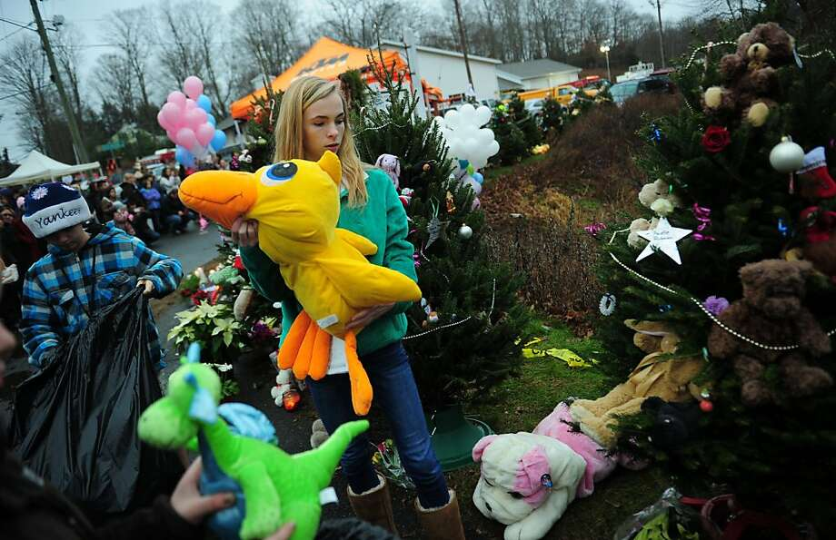 Teenagers decorate Christmas trees set up at a makeshift shrine to the victims of a elementary school shooting in Newtown, Connecticut, December 16, 2012.  A young gunman slaughtered 20 small children and six teachers on December 14,2012 after walking into a school in an idyllic Connecticut town wielding at least two sophisticated firearms. AFP PHOTO/Emmanuel DUNANDEMMANUEL DUNAND/AFP/Getty Images Photo: Emmanuel Dunand, AFP/Getty Images