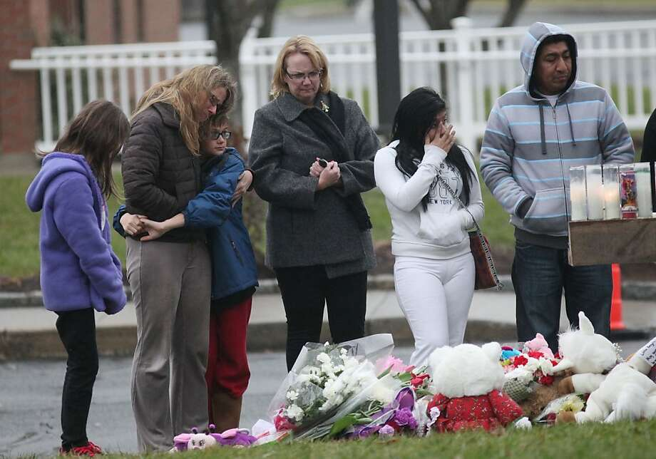 People bring flowers to a memorial outside of St. Rose of Lima Church in the Sandy Hook section of Newtown, Conn. on Sunday, Dec. 16, 2012. Photo: BK Angeletti, B.K. Angeletti