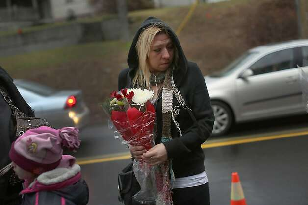 NEWTOWN, CT - DECEMBER 16:  A  woman pauses at a memorial down the street from the Sandy Hook School December 16, 2012 in Newtown, Connecticut. Twenty-six people were shot dead, including twenty children, after a gunman identified as Adam Lanza opened fire at Sandy Hook Elementary School. Lanza also reportedly had committed suicide at the scene. A 28th person, believed to be Nancy Lanza, found dead in a house in town, was also believed to have been shot by Adam Lanza.  (Photo by Spencer Platt/Getty Images) Photo: Spencer Platt, Getty Images