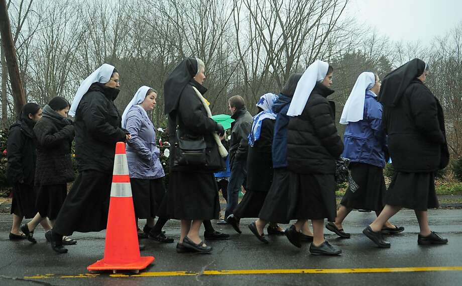 A group of nuns leave after paying their respects at a makeshift shrine to the victims of a elementary school shooting in Newtown, Connecticut, December 16, 2012.  A young gunman slaughtered 20 small children and six teachers on December 14,2012 after walking into a school in an idyllic Connecticut town wielding at least two sophisticated firearms. AFP PHOTO/Emmanuel DUNANDEMMANUEL DUNAND/AFP/Getty Images Photo: Emmanuel Dunand, AFP/Getty Images