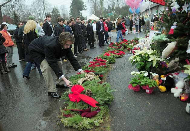 People place holiday wreaths at a makeshift shrine to the victims of a elementary school shooting in Newtown, Connecticut, December 16, 2012.  A young gunman slaughtered 20 small children and six teachers on December 14,2012 after walking into a school in an idyllic Connecticut town wielding at least two sophisticated firearms. AFP PHOTO/Emmanuel DUNANDEMMANUEL DUNAND/AFP/Getty Images Photo: Emmanuel Dunand, AFP/Getty Images