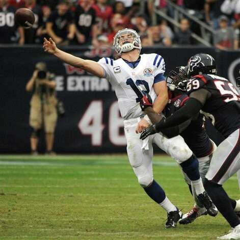 Indianapolis Colts quarterback Andrew Luck (12) is tackled by Houston Texans' Antonio Smith, center, while trying to throw as Whitney Mercilus (59) defends in the fourth quarter of an NFL football game, Sunday, Dec. 16, 2012, in Houston. Luck was called for intentional grounding on the play. The Texans won 29-17. (AP Photo/Dave Einsel) Photo: Dave Einsel, Associated Press / FR43584 AP