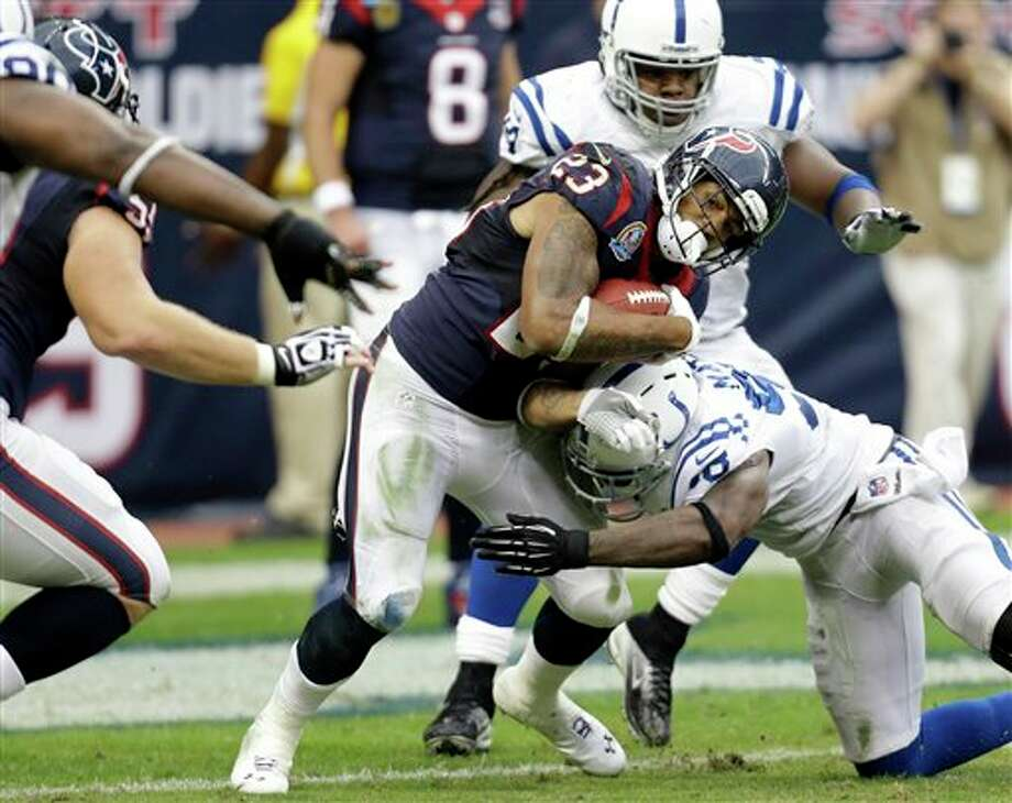 Houston Texans running back Arian Foster (23) is tackled by Indianapolis Colts' Robert Mathis (98) in the second quarter of an NFL football game Sunday, Dec. 16, 2012, in Houston. (AP Photo/Eric Gay) Photo: Eric Gay, Associated Press / AP