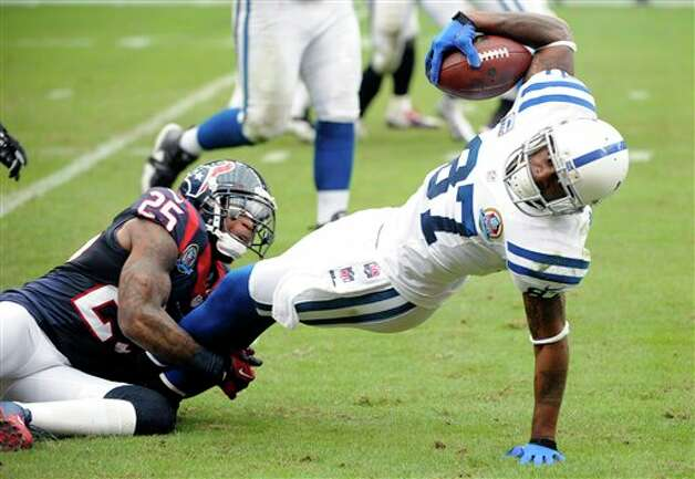 Indianapolis Colts wide receiver Reggie Wayne (87) is tackled by Houston Texans cornerback Kareem Jackson (25) in the second quarter of an NFL football game on Sunday, Dec. 16, 2012, in Houston. (AP Photo/Dave Einsel) Photo: Dave Einsel, Associated Press / FR43584 AP