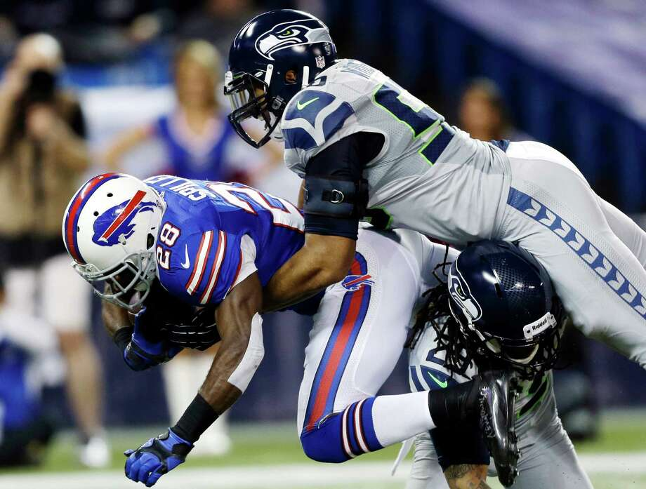 Buffalo Bills running back C.J. Spiller (28) is tackled by Seattle Seahawks free safety Earl Thomas (29) and outside linebacker K.J. Wright (50) during the first half of an NFL football game, Sunday, Dec. 16, 2012, in Toronto. Photo: AP