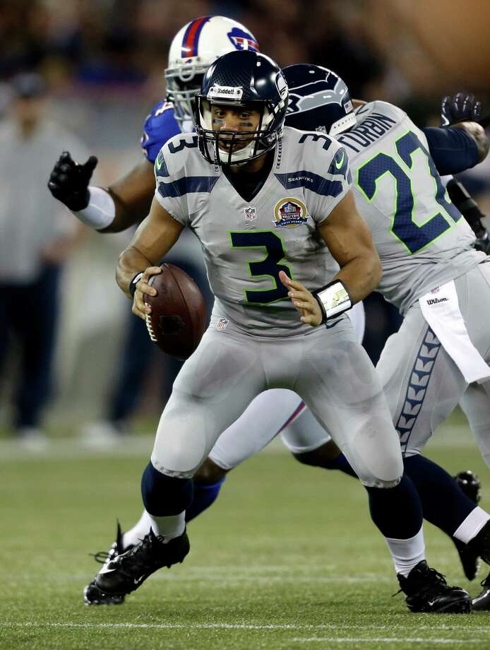 Seattle Seahawks quarterback Russell Wilson (3) runs from Buffalo Bills defenders during the first half of an NFL football game on Sunday, Dec. 16, 2012, in Toronto. Photo: AP