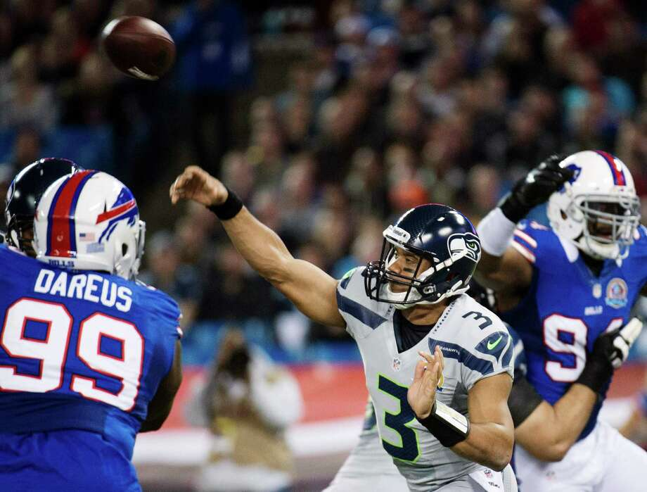Seattle Seahawks quarterback Russell Wilson (3) throws the ball under pressure from Buffalo Bills defensive tackle Marcell Dareus (99) during the first the half of an NFL football game in Toronto, Sunday, Dec. 16, 2012. Photo: AP