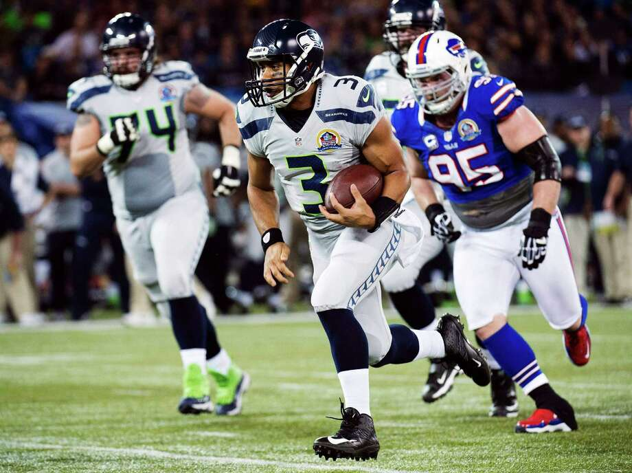 Seattle Seahawks quarterback Russell Wilson (3) runs for a touchdown ahead of Buffalo Bills defensive tackle Kyle Williams (95) during the first the half of an NFL football game in Toronto, Sunday, Dec. 16, 2012. Photo: AP
