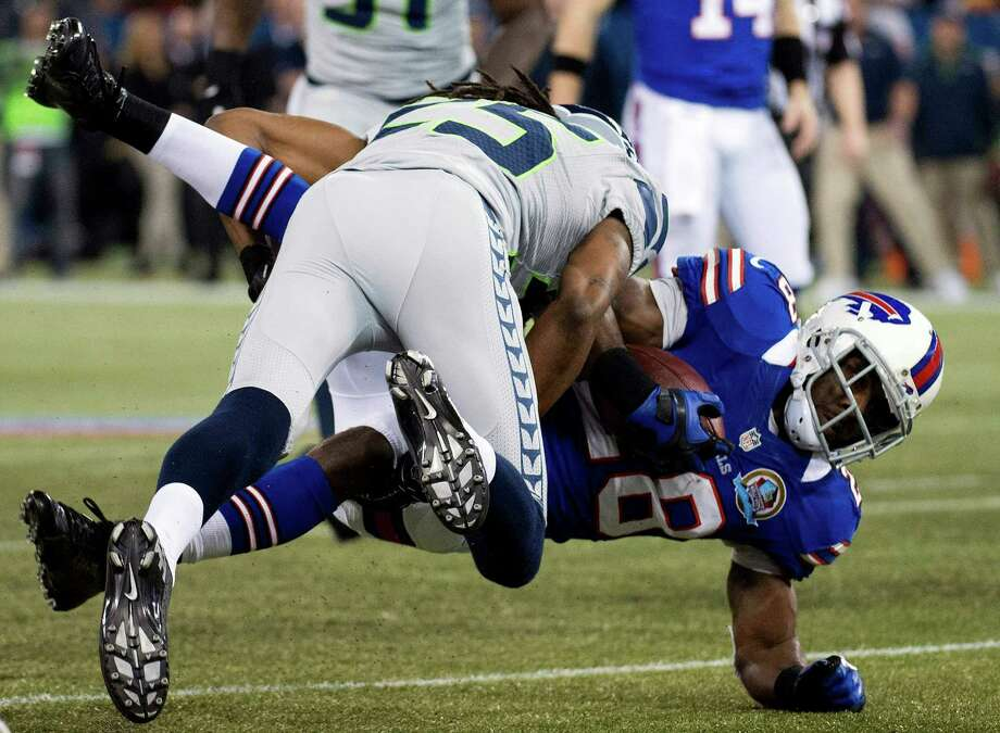 Buffalo Bills running back C.J. Spiller, right, is tackled by Seattle Seahawks cornerback Richard Sherman, left, during the first the half of an NFL football game in Toronto, Sunday, Dec. 16, 2012. Photo: AP