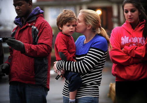 Christine Tunick, of Ridgefield, kisses her son Dillon, 3, during a visit to the large memorial for victims of the Sandy Hook Elementary School shooting on Washington Avenue in the Sandy Hook section of Newtown on Sunday, December 16, 2012. Photo: Brian A. Pounds / Connecticut Post