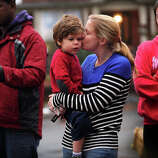 Christine Tunick, of Ridgefield, kisses her son Dillon, 3, during a visit to the large memorial for victims of the Sandy Hook Elementary School shooting on Washington Avenue in the Sandy Hook section of Newtown on Sunday, December 16, 2012.