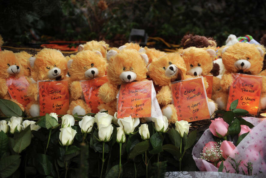 Teddy bears carrying the names and ages of all twenty children slain line the large memorial for vic