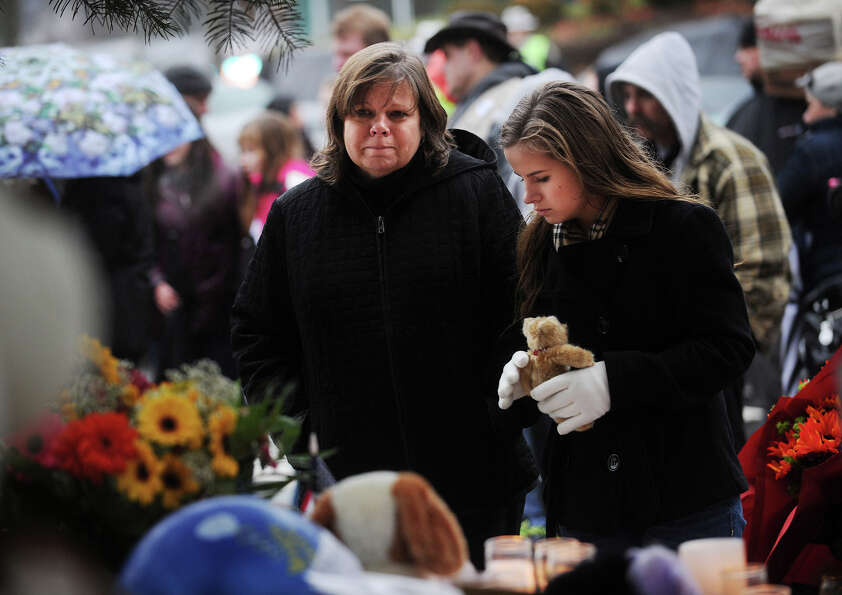 Lori Candela, of Monroe, and her daughter Kyra, 16, visit the large memorial for victims of the Sand