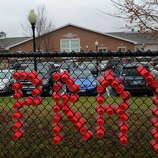 """Cups spell out the word """"pray"""" on the fence outside Read Intermediate School in Newtown, the site of grief counseling for the Sandy Hook Elementary School shooting on Sunday, December 16, 2012."""