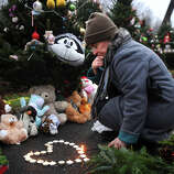 Tracy Kirk of Southbury lights candles in the shape of a heart outside the entrance to Sandy Hook Elementary School in Newtown on Sunday, December 16, 2012.