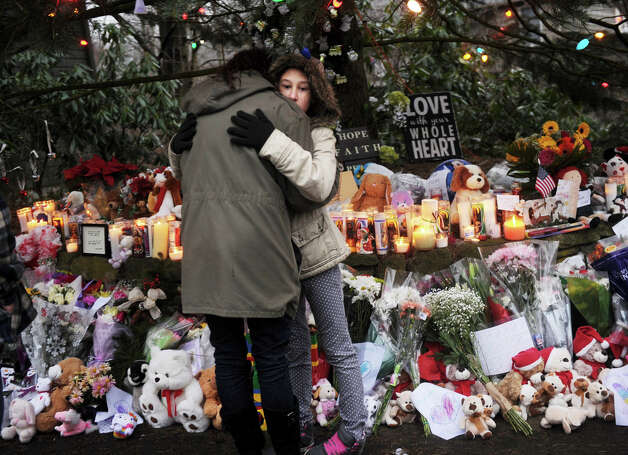 Ellen Renjilian, of Newtown, hugs her daughter Justine, 11, during a visit to the large memorial for victims of the Sandy Hook Elementary School shooting on Washington Avenue in the Sandy Hook section of Newtown on Sunday, December 16, 2012. Photo: Brian A. Pounds / Connecticut Post