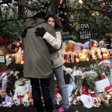 Ellen Renjilian, of Newtown, hugs her daughter Justine, 11, during a visit to the large memorial for victims of the Sandy Hook Elementary School shooting on Washington Avenue in the Sandy Hook section of Newtown on Sunday, December 16, 2012.