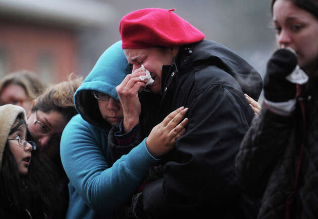 Carmen Cohen weeps as she is comforted by her neice, Jelsey Romero, 16, both of Danbury, during a visit to the large memorial for victims of the Sandy Hook Elementary School shooting on Washington Avenue in the Sandy Hook section of Newtown on Sunday, December 16, 2012.  At left are Elizabeth, 9, and Maria Romero, also of Danbury. Photo: Brian A. Pounds / Connecticut Post